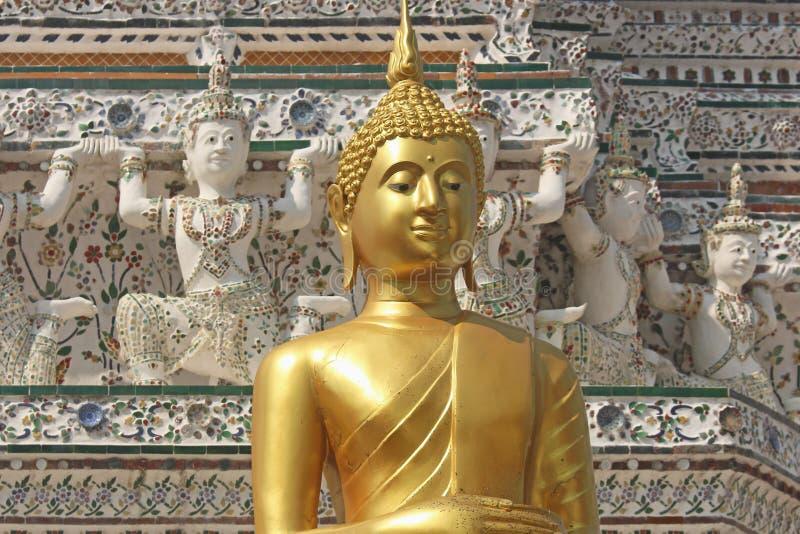 Het gouden standbeeld van Boedha met achtergrond van decoratieve cijfers aangaande stupa in Wat Arun Bangkok, Thailand stock foto's