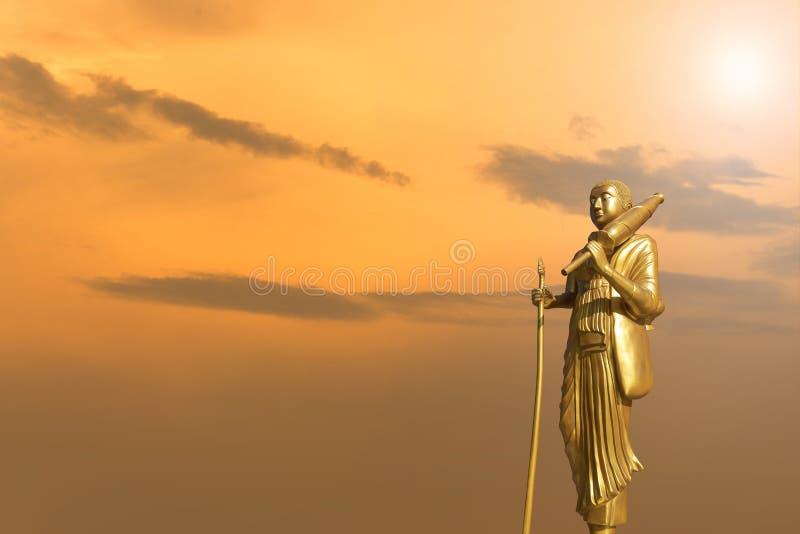 Het gouden standbeeld van Boedha op de achtergrond van de zonsonderganghemel royalty-vrije stock fotografie