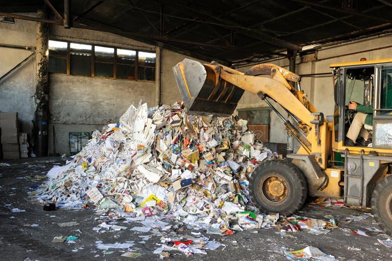 Het graafwerktuig dumpt kartonhuisvuil bij afval recyclingsinstallatie stock afbeeldingen