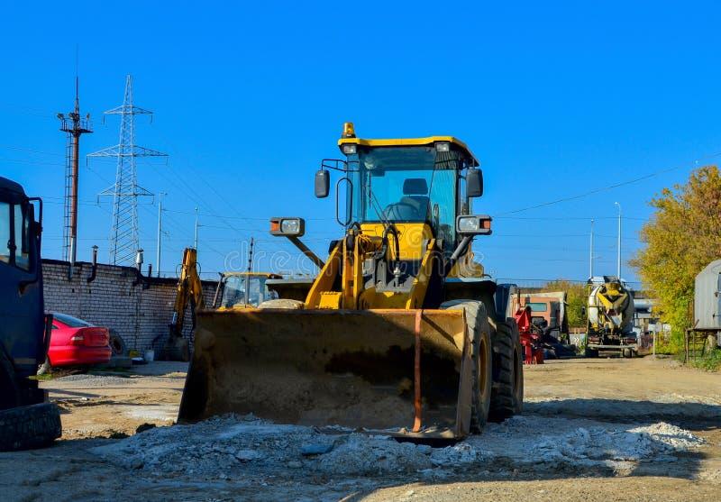 Het graafwerktuig op de bouwwerf treft voorbereidingen om de grond in de stortplaatsvrachtwagen te laden Wiellader met ijzeremmer royalty-vrije stock afbeelding