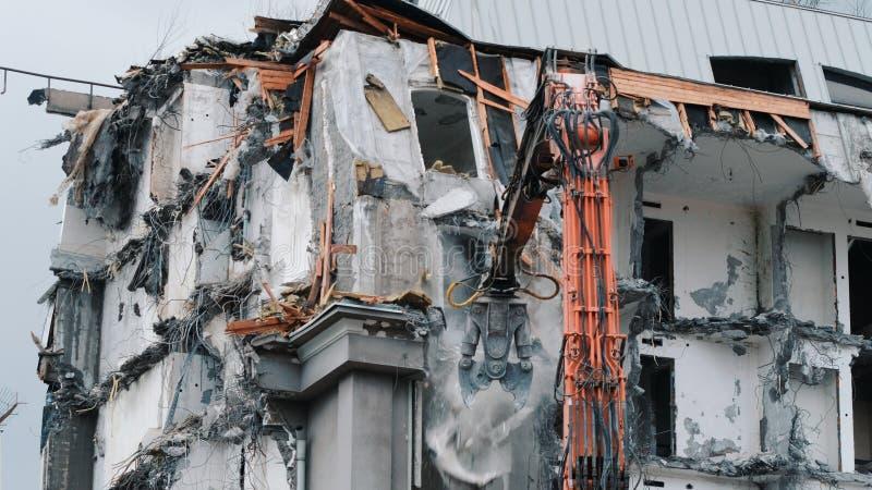 Het graafwerktuig vernietigt het oude gebouw Het vernielingswerk, stukken van beton en versterkingsdaling neer royalty-vrije stock foto
