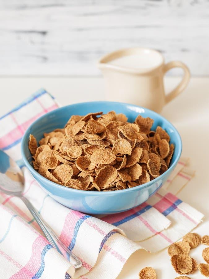Het graangewas van het de zemelenontbijt van het tarweboekweit met melk in ceramische kom stock foto