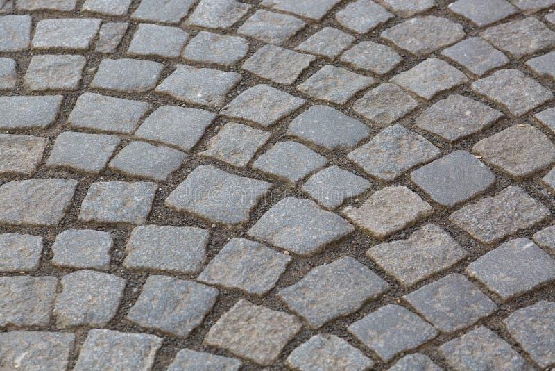 Het graniet cobblestoned bestratingsachtergrond De textuur van de steenbestrating Abstracte achtergrond van het oude close-up van stock foto's