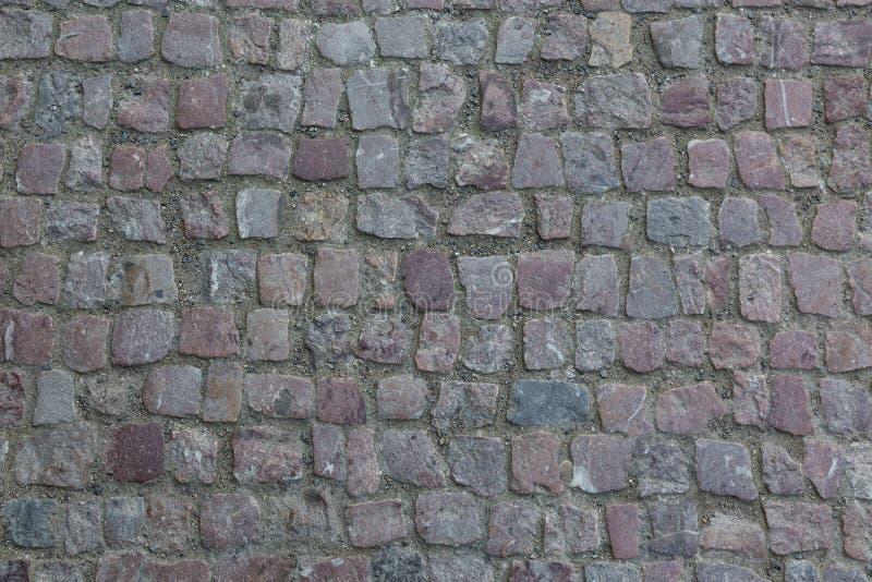 Het graniet cobblestoned bestratingsachtergrond De textuur van de steenbestrating Abstracte achtergrond van het oude close-up van royalty-vrije stock fotografie
