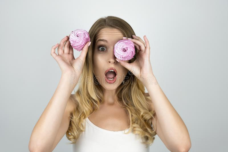 Het grappige aantrekkelijke meisje met één cupcake die dichtbij oog een andere cupcake in haar hand houden kijkt verrast geïsolee stock afbeelding