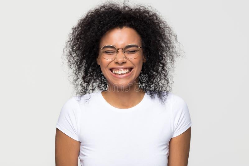 Het grappige Afrikaanse vrouw lachen geïsoleerd op witte grijze studioachtergrond stock fotografie