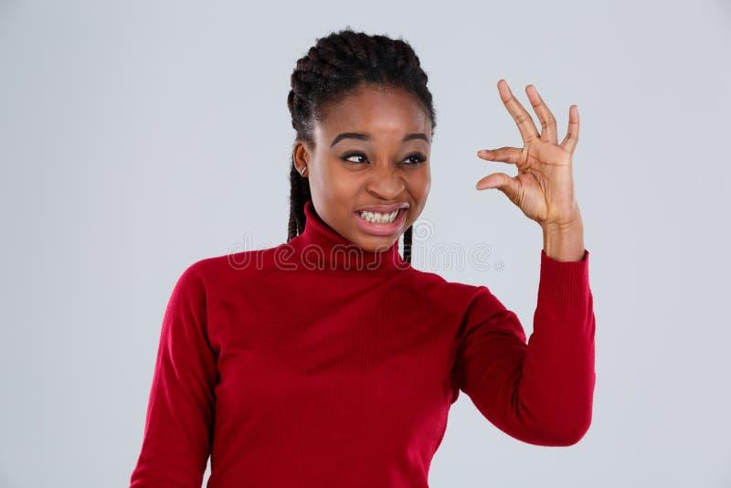Het grappige Afro-Amerikaanse gezicht van meisjesgrimassen en toont duimen omhoog kleine grootte stock fotografie