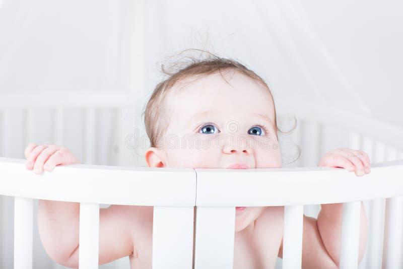 Het grappige baby bijten op een voederbak royalty-vrije stock afbeelding