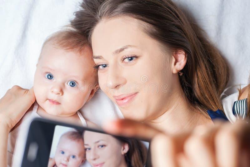 Het grappige babymeisje met mamma maakt selfie op mobiele telefoon stock fotografie