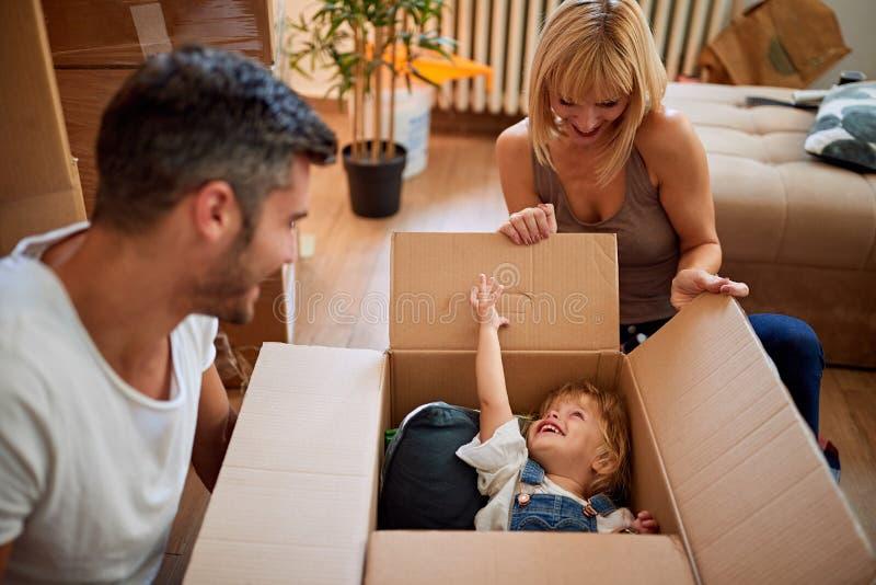 Het grappige bewegen zich aan een nieuw huis - de familie beweegt dozen in een nieuw huis stock fotografie
