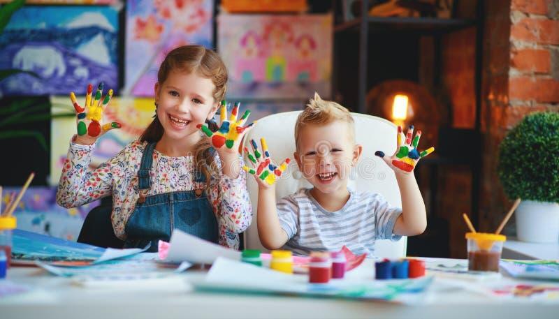 Het grappige de kinderenmeisje en jongen trekken het lachen tonen handen vuil met verf stock foto