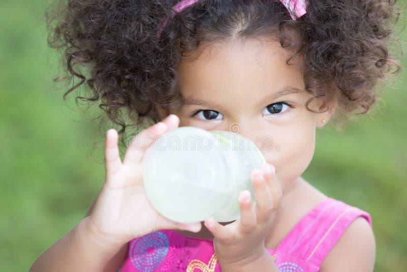Het grappige en leuke Latijnse meisje drinken van een zuigfles stock afbeelding