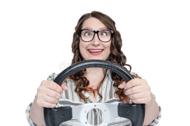 Het grappige gelukkige meisje in glazen en de ogen in een hoop met auto rijden, geïsoleerd op witte achtergrond, autoconcept royalty-vrije stock foto