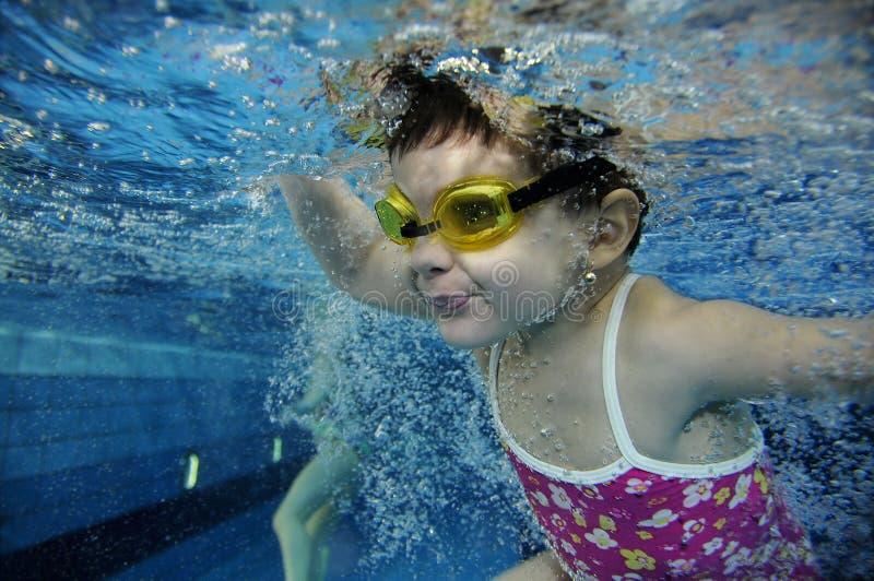 Het grappige gelukkige peutermeisje zwemmen onderwater in een pool met veel luchtbellen stock foto's