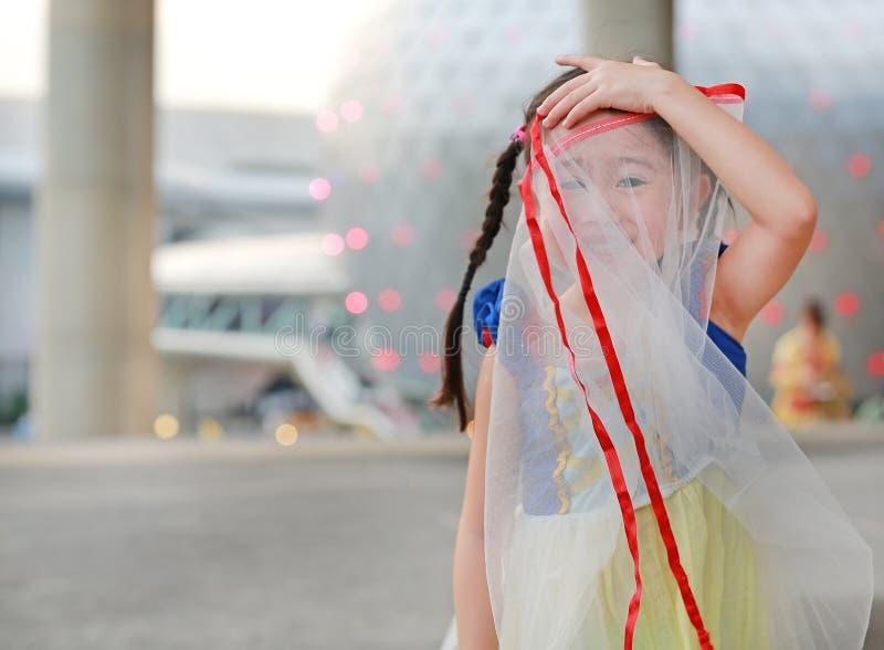 Het grappige gezicht van weinig Aziatisch kindmeisje die rok gebruiken beschermt haar gezicht royalty-vrije stock foto