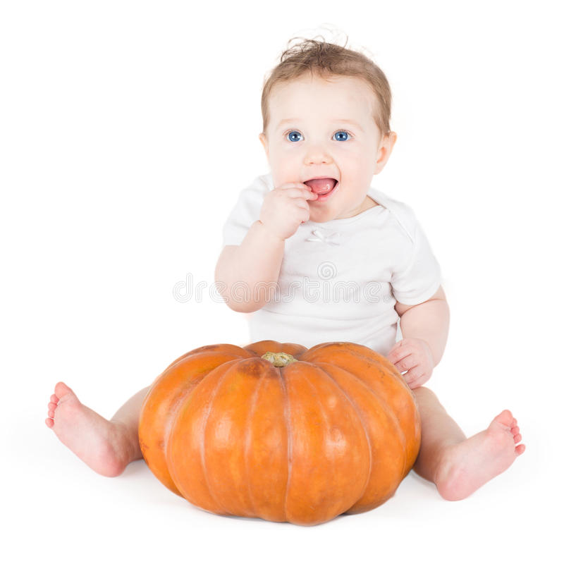 Het grappige het lachen babymeisje spelen met reusachtige pompoen royalty-vrije stock afbeelding