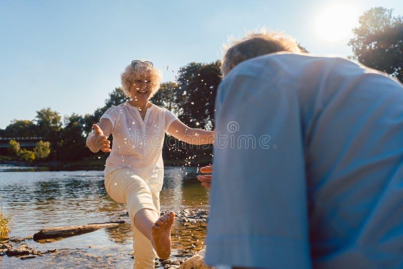 Het grappige hogere paar spelen met water bij de rivier in een zonnige dag van de zomer stock afbeeldingen