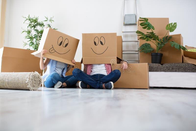 Het grappige jonge paar genieten van en het vieren het bewegen zich aan nieuw huis stock afbeeldingen