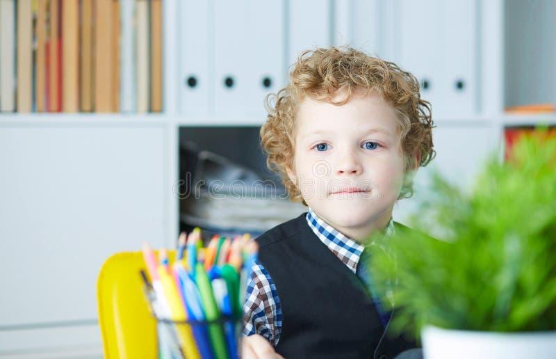 Het grappige kind kijkt als een werkgever op een ondergeschikte weinig werkgever in bureau royalty-vrije stock fotografie