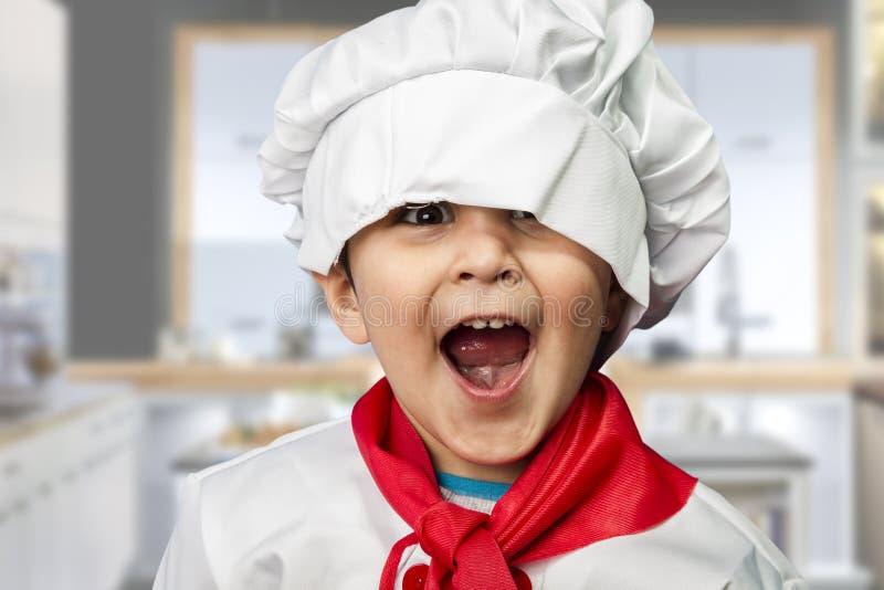 Het grappige kind kleedde zich als kok stock afbeeldingen