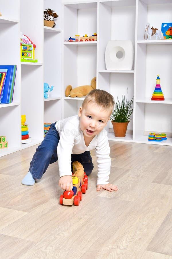Het grappige kind spelen met een houten trein stock foto