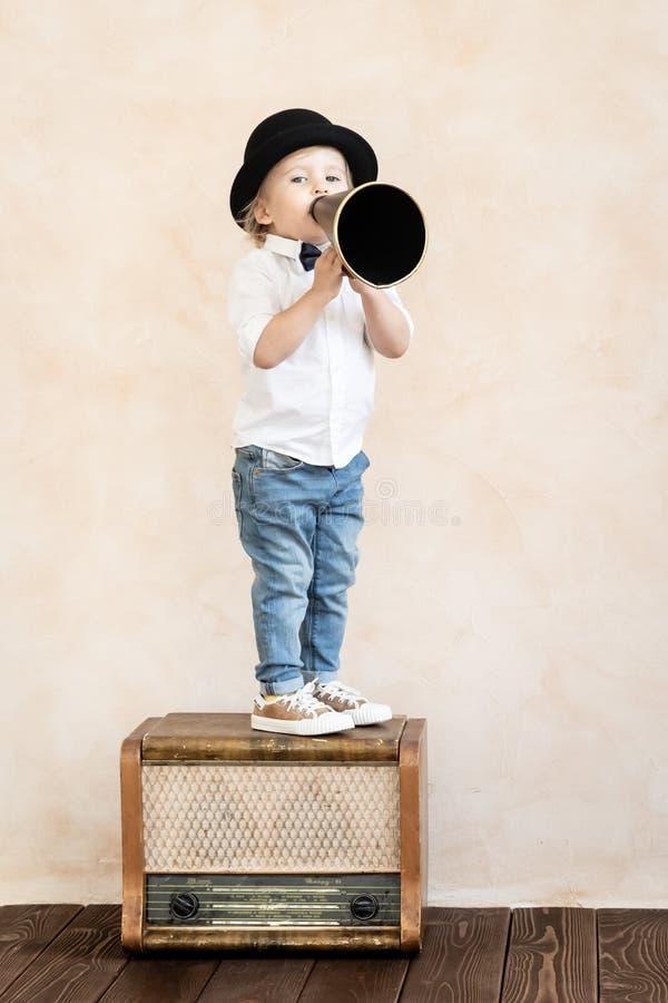 Het grappige kind spelen met zwarte retro megafoon royalty-vrije stock afbeeldingen
