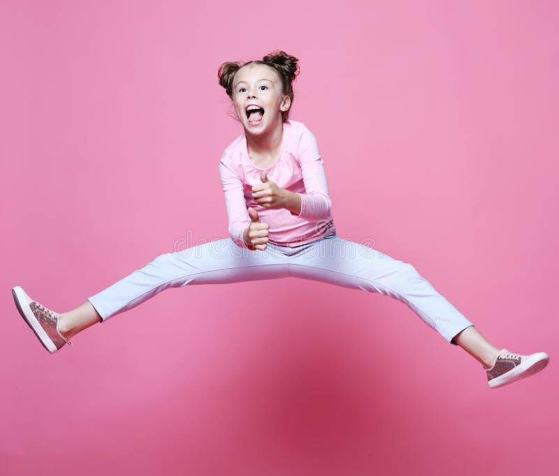 het grappige kindmeisje kleedde het toevallige springen op roze achtergrond stock afbeelding