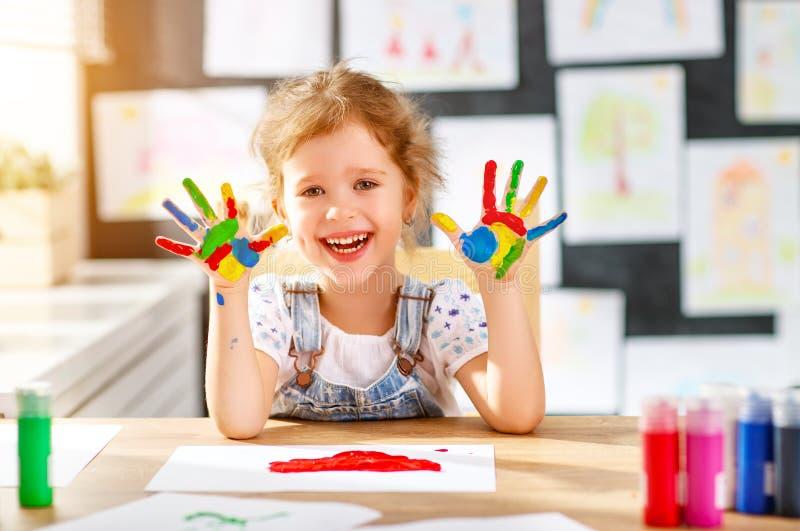 Het grappige kindmeisje trekt het lachen toont handen vuil met verf royalty-vrije stock foto