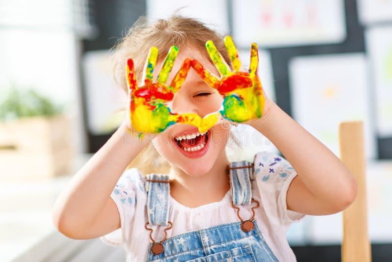 Het grappige kindmeisje trekt het lachen toont handen vuil met verf royalty-vrije stock fotografie