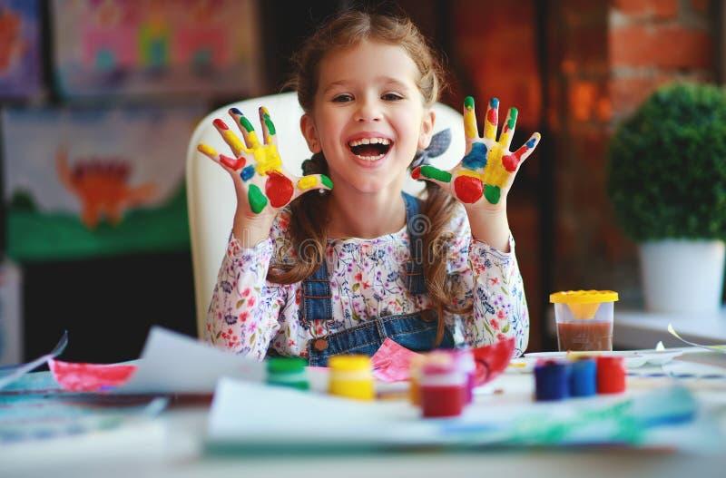 Het grappige kindmeisje trekt het lachen toont handen vuil met verf royalty-vrije stock afbeeldingen