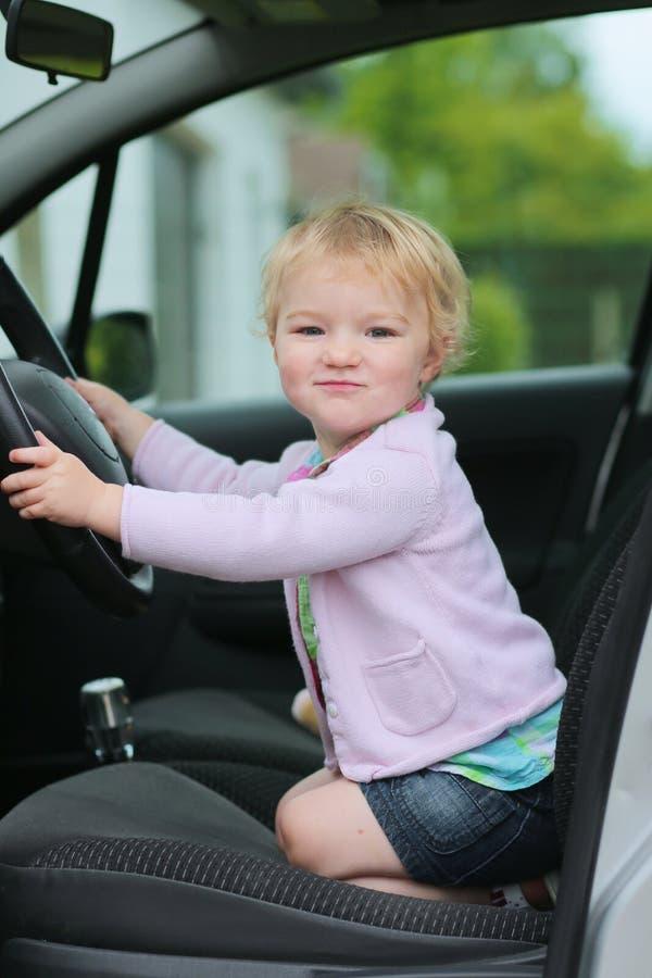 Het grappige kleutermeisje spelen in de auto stock afbeeldingen