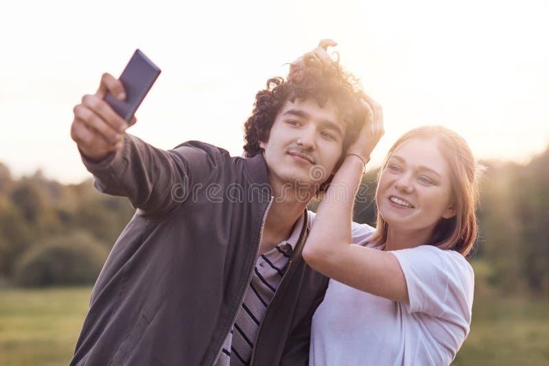 Het grappige krullende mannelijke kereltje en zijn meisje stelt voor het maken van selfie portret tegen vage aardachtergrond, heb royalty-vrije stock fotografie
