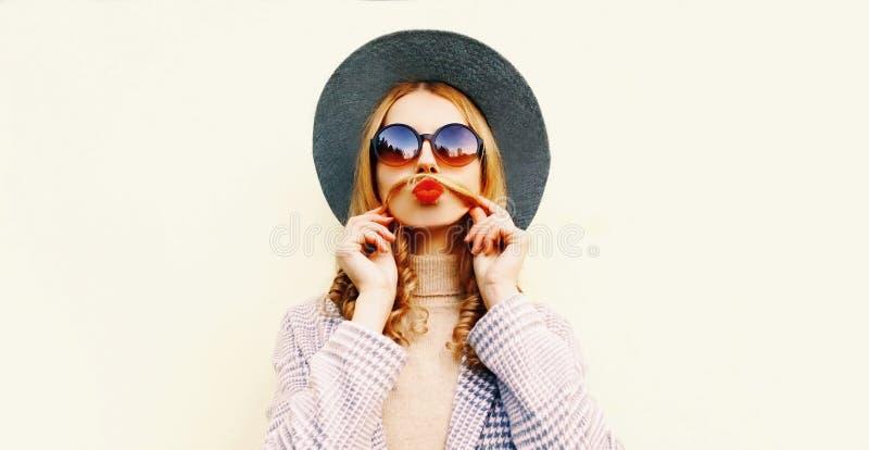 Het grappige meisje die van het portretclose-up snor haar haar tonen die rode lippen blazen die pret in ronde hoed hebben royalty-vrije stock fotografie