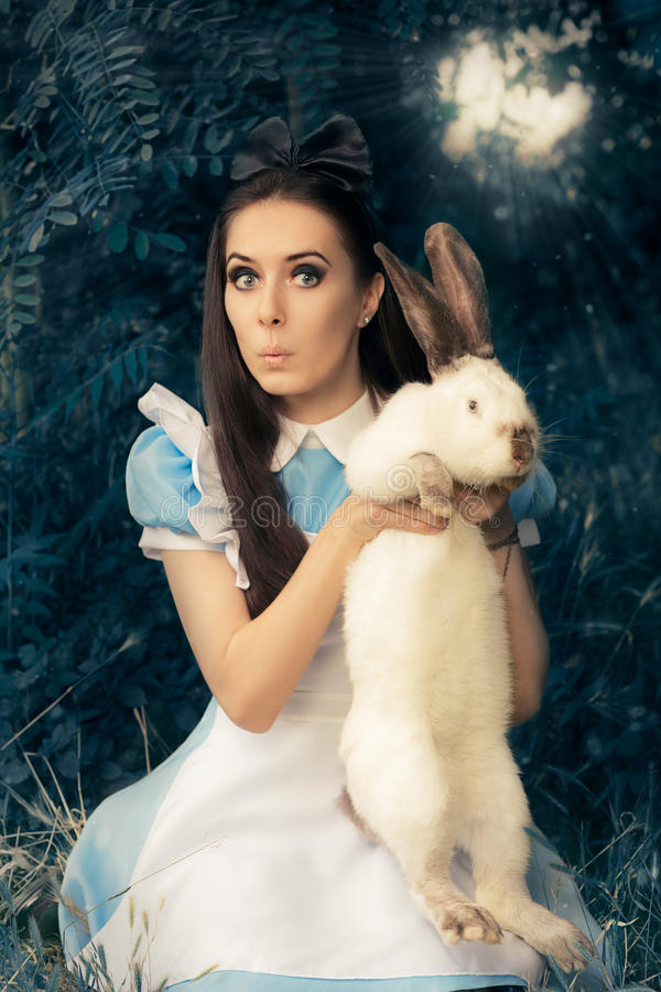 Het grappige Meisje kostumeerde als Alice in Sprookjesland met het Witte Konijn stock afbeeldingen