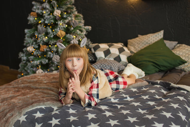 Het grappige meisje ligt op een bed in Kerstmistijd royalty-vrije stock afbeelding