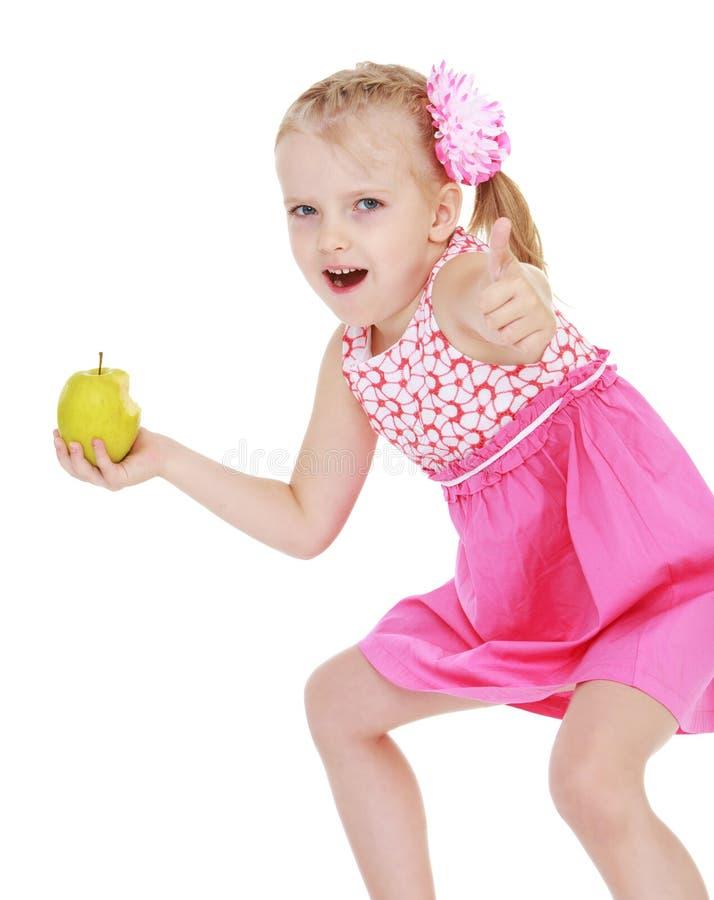 Het grappige meisje met een appel in zijn hand toont royalty-vrije stock afbeeldingen