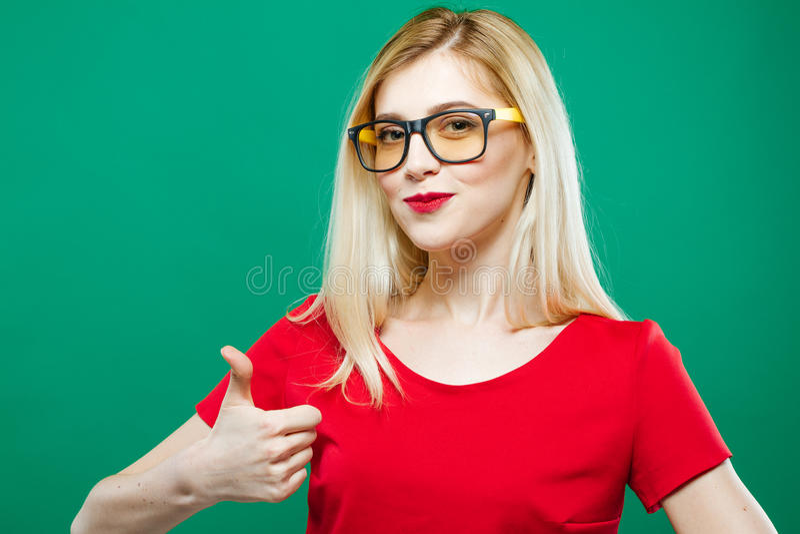 Het grappige Meisje in Oogglazen toont Duim op Groene Achtergrond Mooi Blonde met Lang Haar en Rode Bovenkant in Studio stock foto