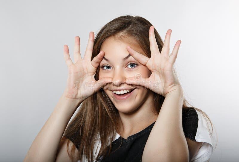 Het grappige meisje opent haar ogen met haar handen stock foto
