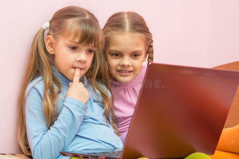 Het grappige meisje zette een vinger in zijn mondzitting bij laptop stock afbeeldingen