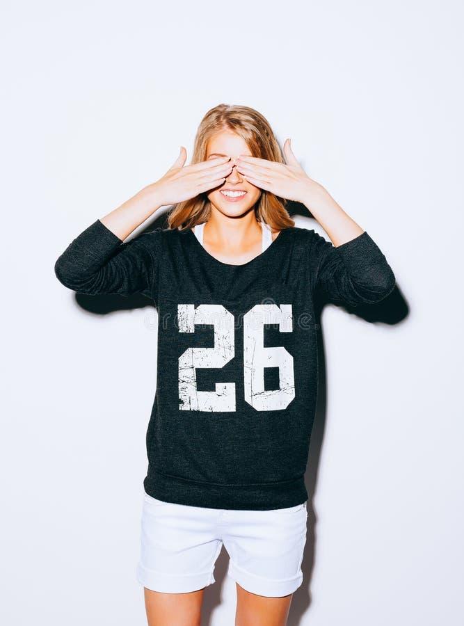 Het grappige mooie blonde gekke meisje van het levensstijlportret sluit ogen met haar handen, in Sweatshirt en witte borrels, die stock foto