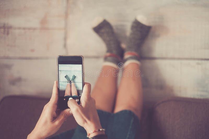 Het grappige mooie meisje die van Nice beelden nemen bij haar voeten met gekke sokken royalty-vrije stock afbeeldingen