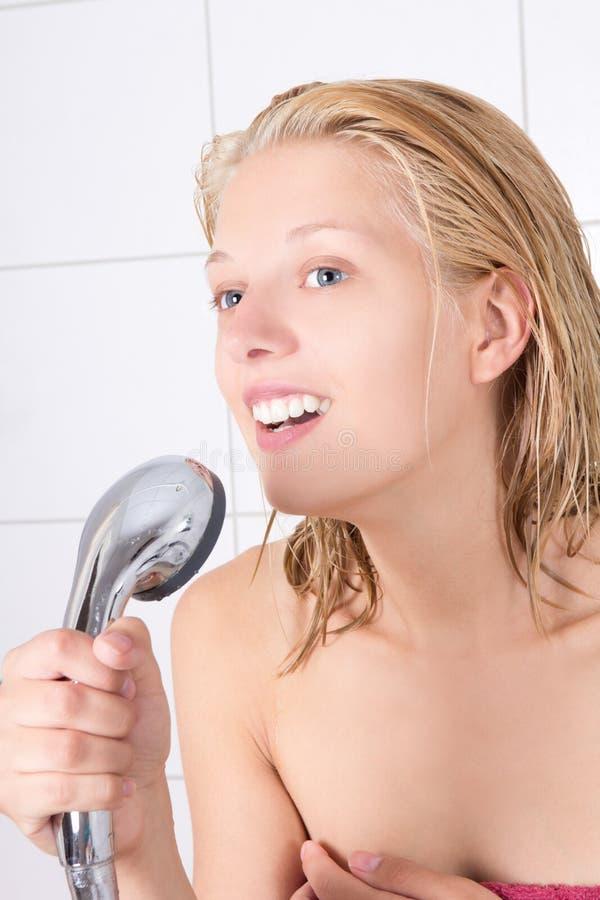 Het grappige mooie meisje zingen in douche stock foto's