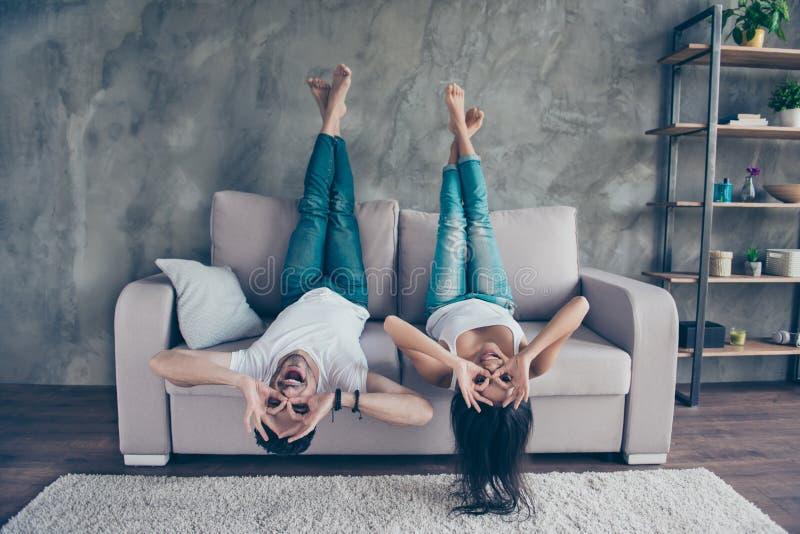 Het grappige paar met glazen het gesturing ligt ondersteboven op stock afbeelding