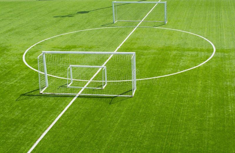 het gras van het voetbalgebied Een groen voetbalgebied als achtergrond stock afbeeldingen