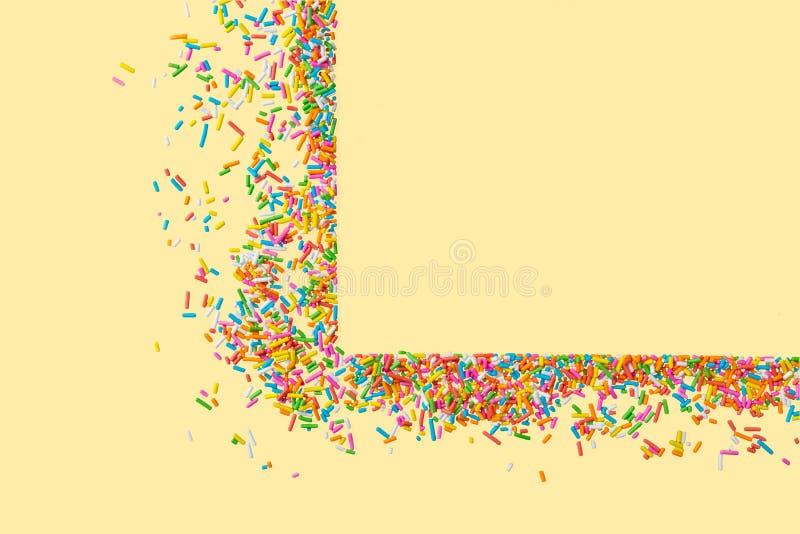 Het grenskader van kleurrijk bestrooit op een gele achtergrond met c royalty-vrije stock afbeeldingen