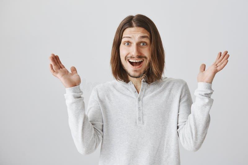 Het grijnzen van geluk en positieve resultaten Portret van tevreden knappe echtgenoot die met baard en lang haar wapens opheffen stock afbeelding