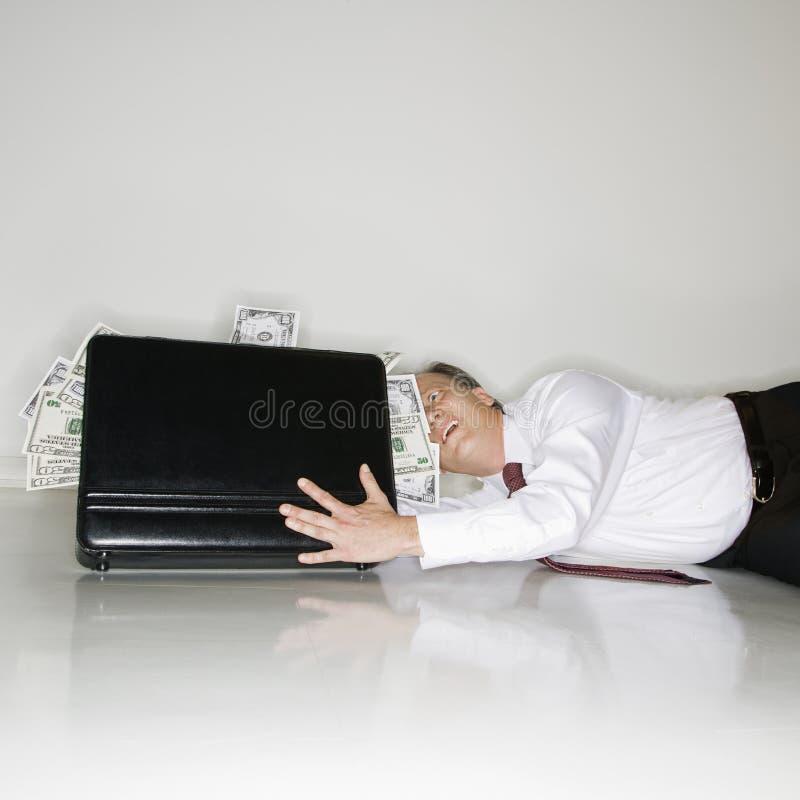 Het grijpen van de zakenman geld stock foto
