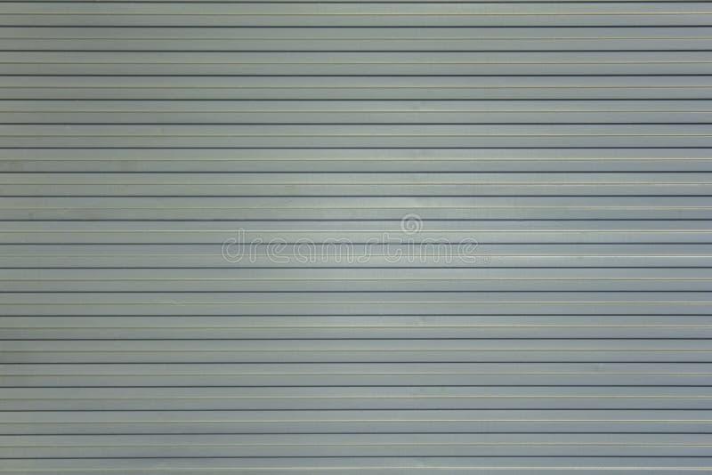 Het grijs-witte blauwe schild van de metaalmuur met horizontale lijnen en schaduwen Ruwe Oppervlaktetextuur stock foto's