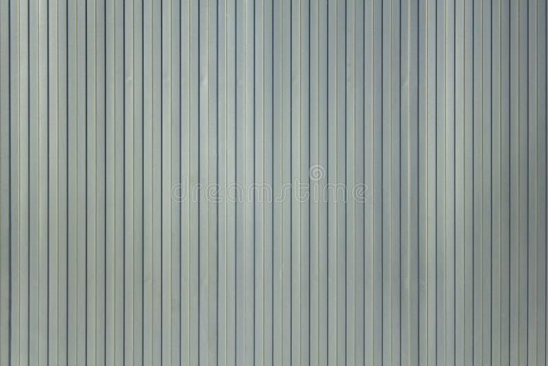 Het grijs-witte blauwe schild van de metaalmuur met verticale lijnen en schaduwen Ruwe Oppervlaktetextuur royalty-vrije stock foto