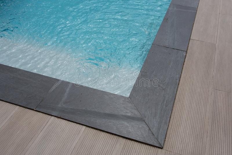 Het grijze bruine detail van het hoek zwembad met treden en blauw water royalty-vrije stock afbeelding